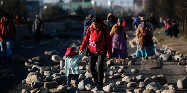 En kvinna och hennes barn går på en blockerad väg i El Alto, Bolivia. Natacha Pisarenko / TT NYHETSBYRÅN