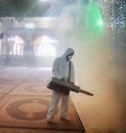 En brandman desinficerar en helgedom i norra Teheran, Iran.  Ebrahim Noroozi / TT NYHETSBYRÅN