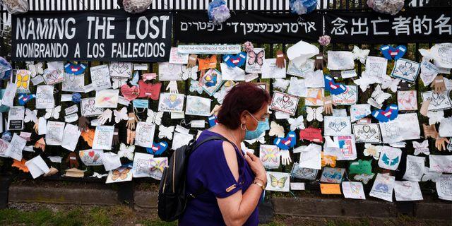Arkivbild: På en kyrkogård i Brooklyn har sörjande satt upp hyllningar till pandemins offer på staketet. Mark Lennihan / TT NYHETSBYRÅN