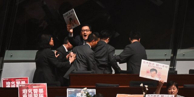 Säkerhetsansvariga för ut en ledamot som protesterade mot Carrie Lams styre i parlamentet under torsdagen. PHILIP FONG / AFP