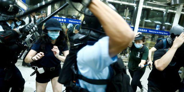 Polisen drabbar samman med demonstranter vid flygplatsen i Hongkong. THOMAS PETER / TT NYHETSBYRÅN
