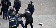 Benalla som iförd ett visir släpar bort en demonstrant, 1 maj, NAGUIB-MICHEL SIDHOM / AFP