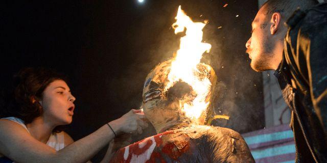 Demonstrant tänder eld på en docka föreställande Donald Trump. Matthew Hinton / TT / NTB Scanpix
