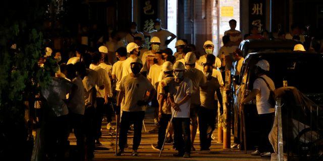 Män i vita t-shirts samlades vid en tågstation.  TYRONE SIU / TT NYHETSBYRÅN