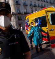 En hälsoarbetare desinfekterar en kollega i Madrid den 28 augusti. Andrea Comas / TT NYHETSBYRÅN