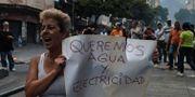 En kvinna håller upp ett plakat om att hon vill ha vatten och el. Flera demonstrerar mot läget som rådet i Venezuela just nu. FEDERICO PARRA / AFP