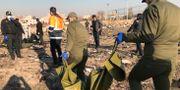 Vrakdelar och räddningsarbetare på olycksplatsen utanför Teheran. WANA NEWS AGENCY / TT NYHETSBYRÅN