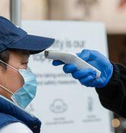 En sjukvårdare tar temperaturen på en man. Mark Baker / TT NYHETSBYRÅN