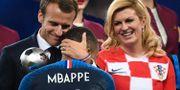 Emmanuel Macron kramar om Kylian Mbappé efter finalen. Till höger Kroatiens president Kolinda Grabar-Kitarović. JEWEL SAMAD / AFP