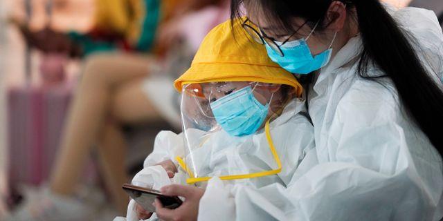 En kvinna i Wuhan med sin telefon och sitt barn. ALY SONG / TT NYHETSBYRÅN