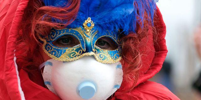 Karnevalbesökare med munskydd. MANUEL SILVESTRI / TT NYHETSBYRÅN