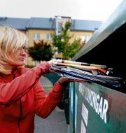 En kvinna återvinner tidningar. PONTUS LUNDAHL / TT / TT NYHETSBYRÅN
