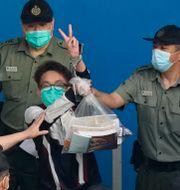 Aktivisten Figo Chan eskorteras till rätten i maj.  Kin Cheung / TT NYHETSBYRÅN