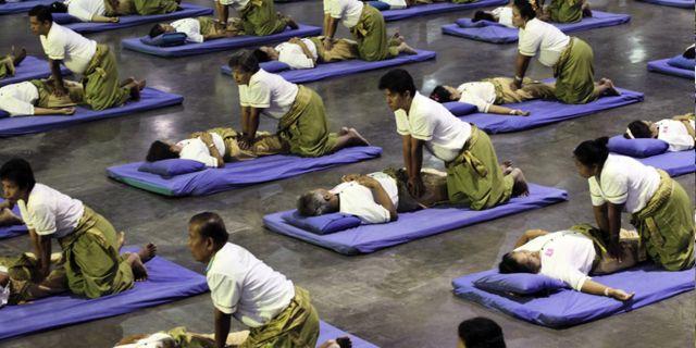 Thaimassörer utför massmassage i en sportarena i utkanten av Bangkok. Apichart Weerawong/TT Nyhetsbyrån
