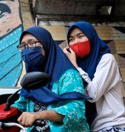 Indonesiska kvinnor med munskydd. Dita Alangkara / TT NYHETSBYRÅN