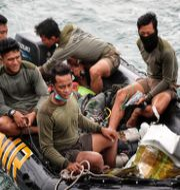 Räddningsarbetare som funnit rester och prylar från flygplanet i går. Azwar Ipank / TT NYHETSBYRÅN
