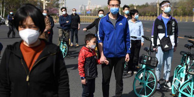 Människor nära Tiananmen-torget i Peking.  GREG BAKER / TT NYHETSBYRÅN