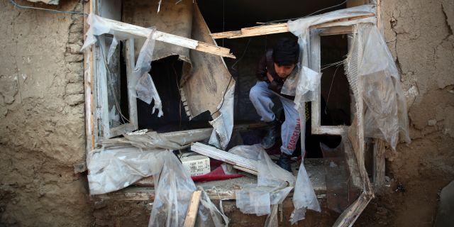 Pojke klättrar ut från sitt hem som skadats i en attack i december 2019.  Rahmat Gul / TT NYHETSBYRÅN
