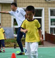 Kinesiska skolbarn tränar fotboll. Arkivbild. HECTOR RETAMAL / AFP